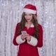 Santas Assistant Looks Into the Smartphone and Smiles. Bokeh Background - VideoHive Item for Sale