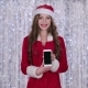 Santa Girl Holds the Phone in Her Hands and Looks Into the Distance. Bokeh Background - VideoHive Item for Sale