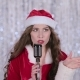 Santa Woman Sings in a Retro Microphone on Bokeh Background - VideoHive Item for Sale