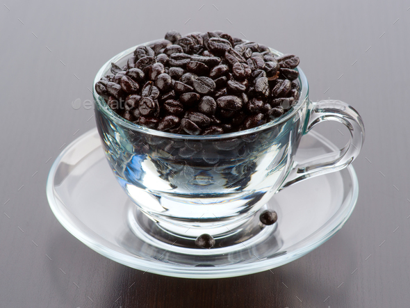 transparent glass cup filled with coffee beans on dark wooden background - Stock Photo - Images