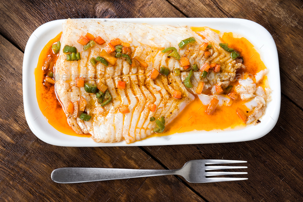 overhead take of fresh cod fillet cooked in classic wood - Stock Photo - Images