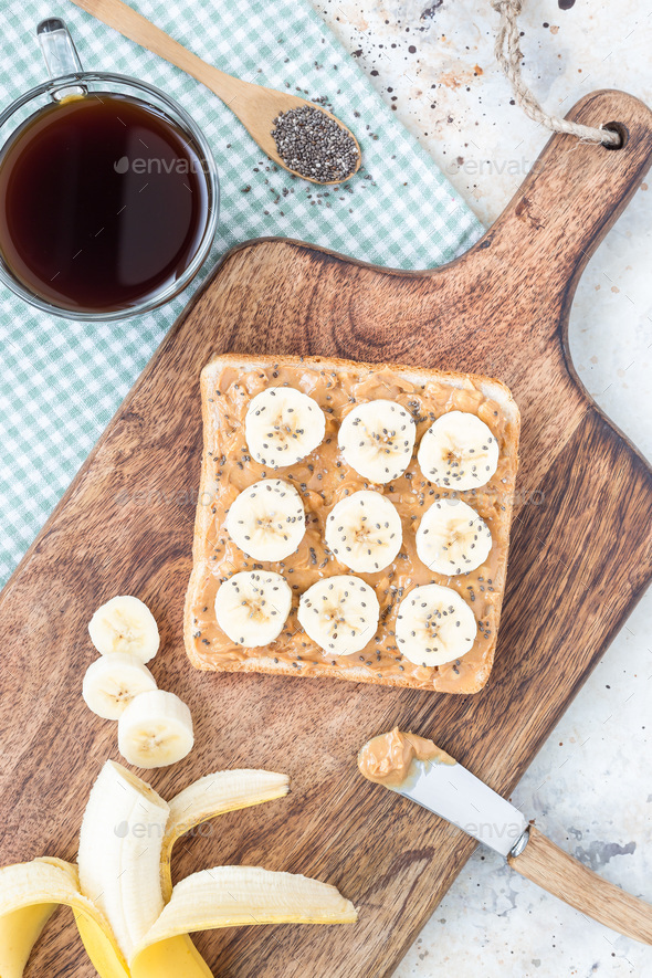 Sandwich with crunchy peanut butter, banana and chia seeds, top view, vertical - Stock Photo - Images