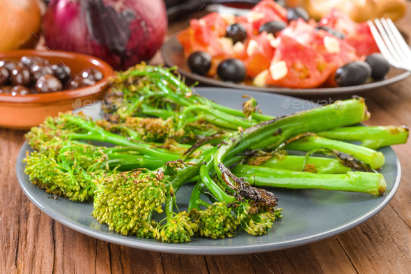 dish with tender shoots of broccoli grilled and tomato salad - Stock Photo - Images