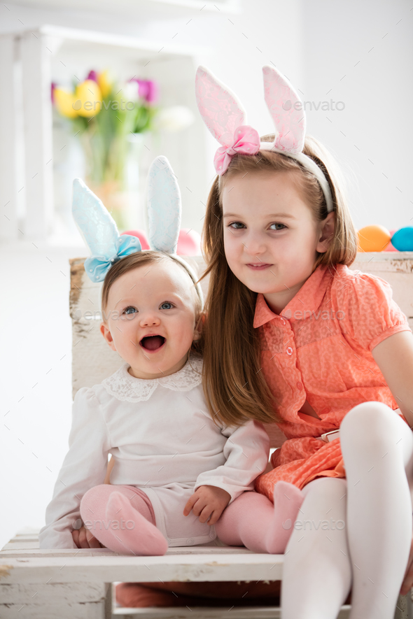 Two sisters in funny bunny costumes sitting together - Stock Photo - Images