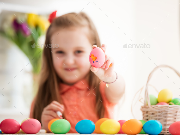 Young girl showing drawing on an egg. - Stock Photo - Images