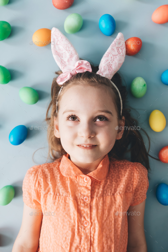 Girl with bunny ears surrounded by colorful eggs. - Stock Photo - Images