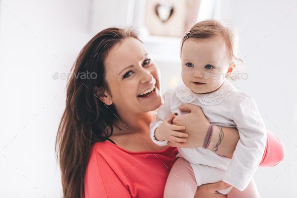 Young mother hugging her baby daughter - Stock Photo - Images