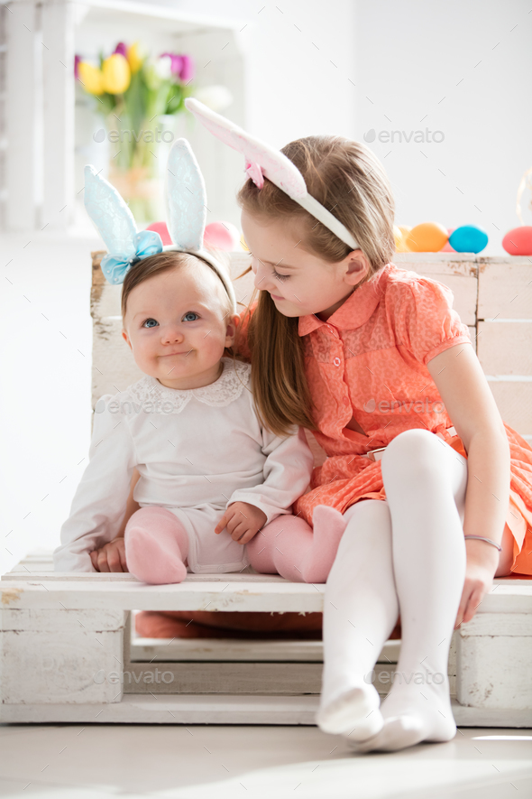 Sibiling in funny bunny ears sitting together. - Stock Photo - Images
