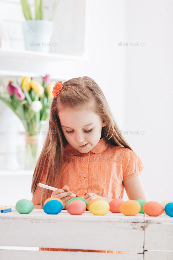 Young focused girl drawing patterns on dyed eggs - Stock Photo - Images