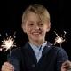 Boy Holds a Sparkler in Both Hands, Smiling on Black Background - VideoHive Item for Sale