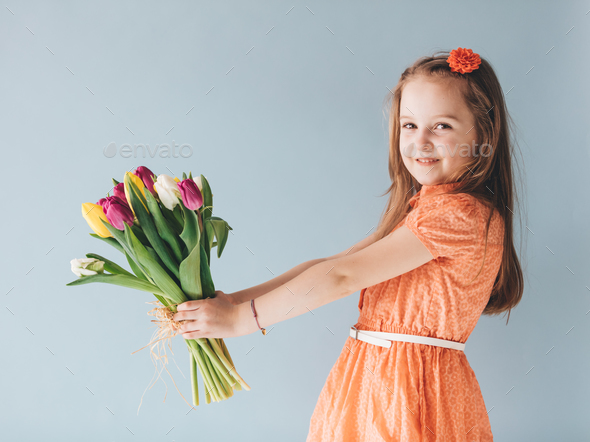 Girl holding a bunch of colorful tulips. - Stock Photo - Images