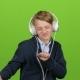 Baby in the Headphones Is Listening to Music on Green Screen - VideoHive Item for Sale
