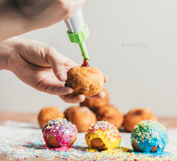 Woman filling homemade doughnut with rose jam - Stock Photo - Images