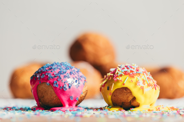 Two decorated doughnuts laying on a table. - Stock Photo - Images
