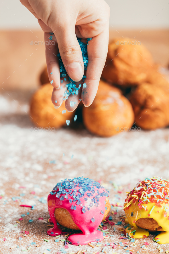 Woman sprinkling sugar strands on doughnuts - Stock Photo - Images