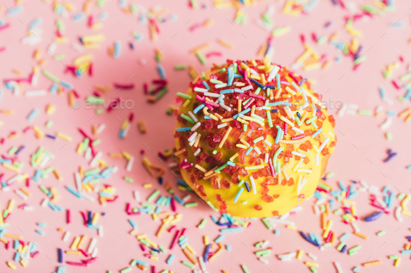 Sprinkled yellow doughnut on pink background. - Stock Photo - Images