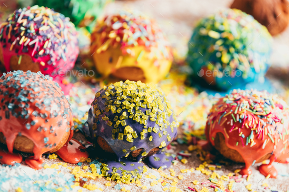 Sprinkled donuts laying on a messy counter - Stock Photo - Images