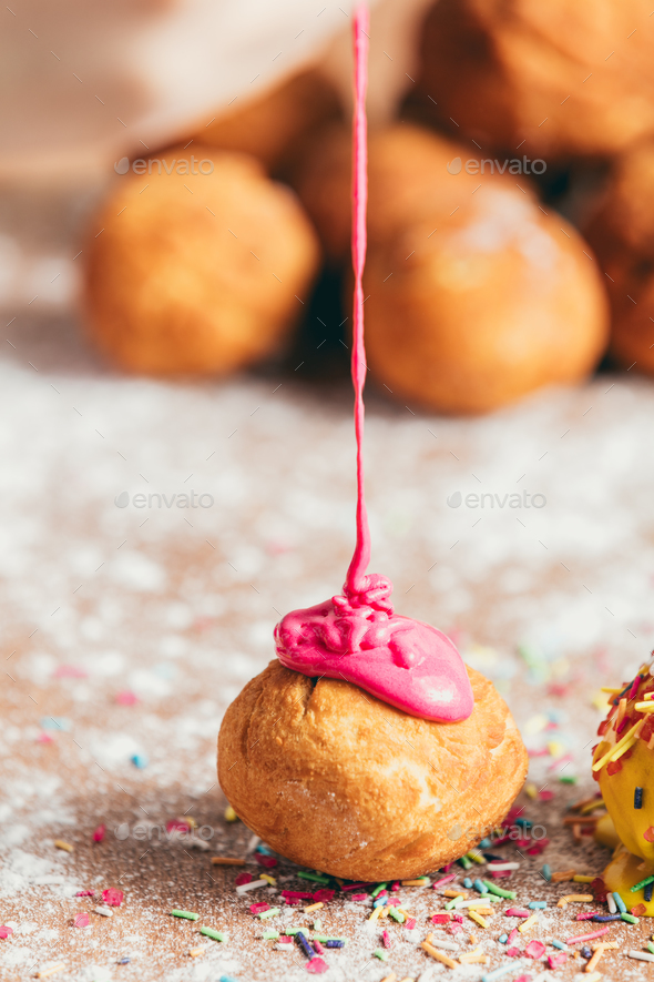 Pink glaze poured down on a little doughnut. - Stock Photo - Images