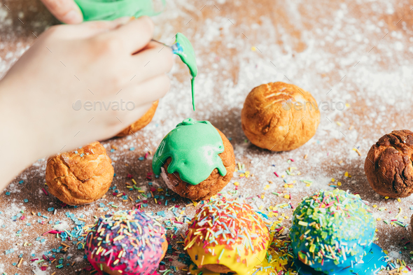 Woman's hand coating a donut with green frosting. - Stock Photo - Images