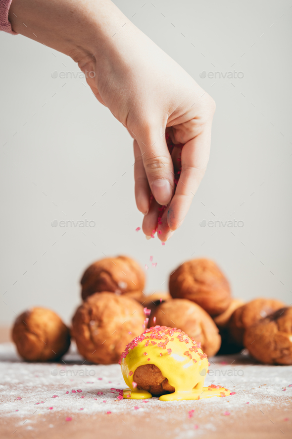 Sprinkling sugar topping on top of a doughnut. - Stock Photo - Images