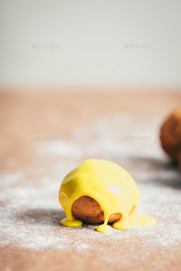 Single doughnut with vivid yellow icing - Stock Photo - Images
