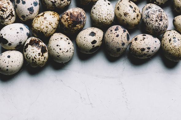 Spotted quail eggs on white marble background. - Stock Photo - Images