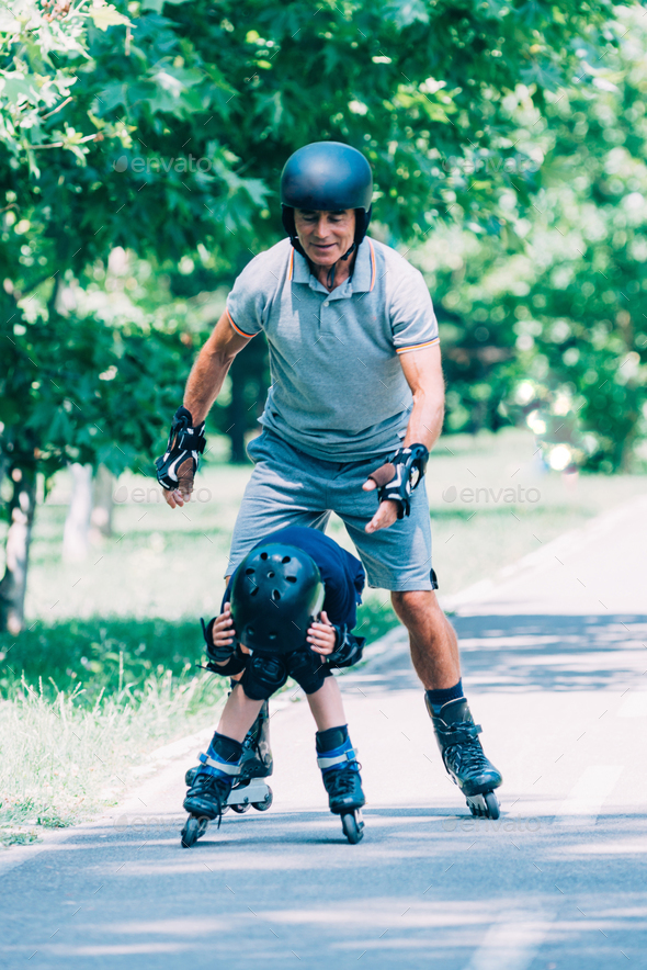 Grandfather and grandson having fun, roller skating in the park - Stock Photo - Images