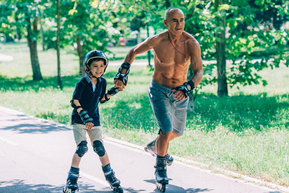 Grandfather and grandson roller skating together - Stock Photo - Images