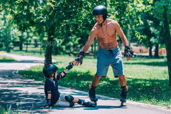 Grandfather giving hand to his grandson after minor roller skati - Stock Photo - Images