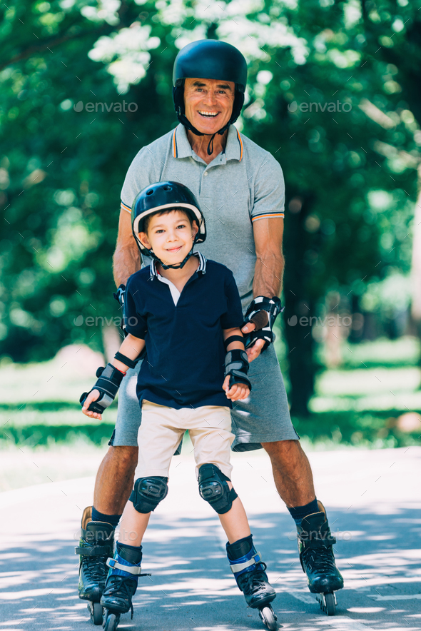 Portrait of grandfather and grandson roller skating in the park - Stock Photo - Images