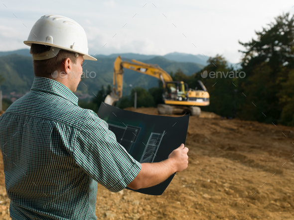 male engineer reading blueprint - Stock Photo - Images