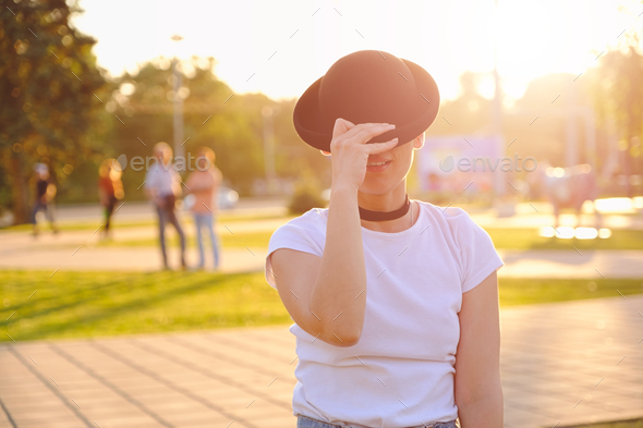 Beautiful woman hiding face behind hat showing eyes - Stock Photo - Images