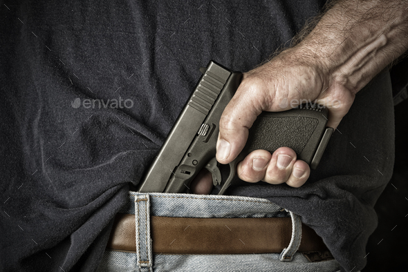 Man pulling gun from waistband - Stock Photo - Images