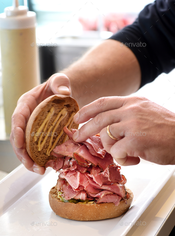 Chef preparing a pastrami sandwich - Stock Photo - Images