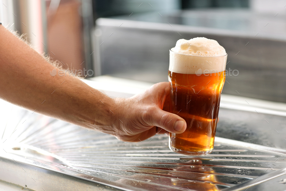 Man holding a fresh glass of chilled draft beer - Stock Photo - Images