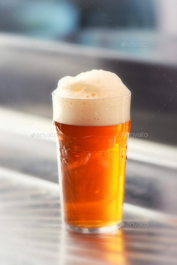 Fresh served pint of frothy draft beer in a glass - Stock Photo - Images