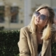 Young Beautiful Blonde Girl in Casual Clothes and Sunglasses Sitting on a Bench in a City Park - VideoHive Item for Sale