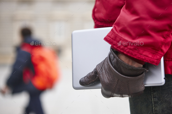 Woman holding a tablet in a city downtown. Winter time - Stock Photo - Images