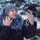 Girl Corrects Make-up in the Winter Snow-covered Park - VideoHive Item for Sale