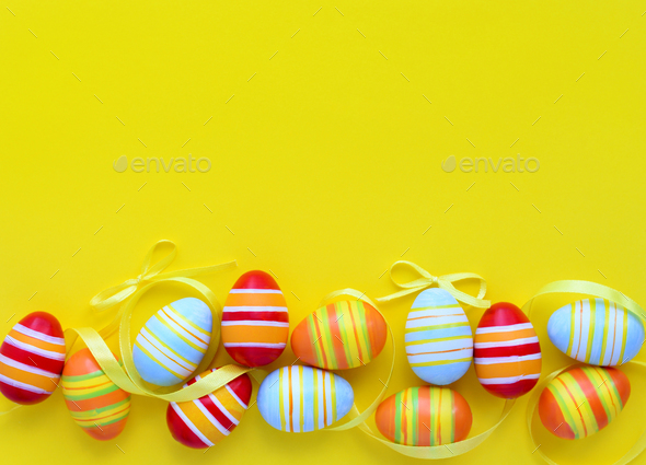 Colorful easter eggs and ribbons on a yellow background with emp - Stock Photo - Images