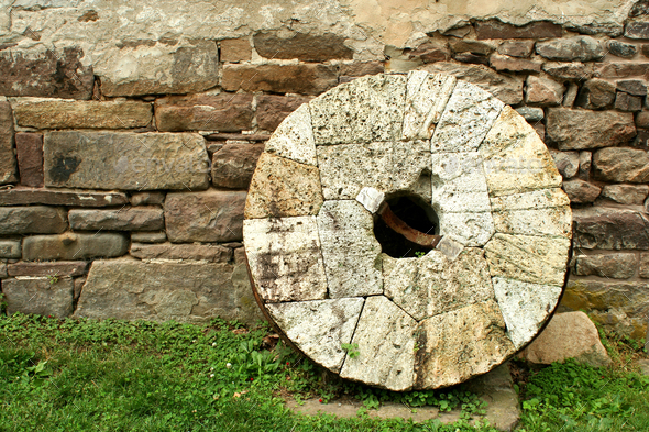 Old millstone leaning on a wall - Stock Photo - Images