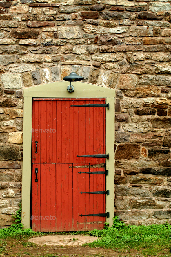 Red door on a old stone building - Stock Photo - Images