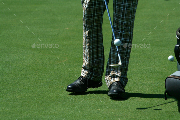 Golfer juggling a golf ball with retro pants - Stock Photo - Images