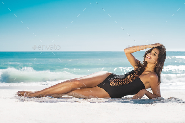 Smiling woman lying on sand - Stock Photo - Images