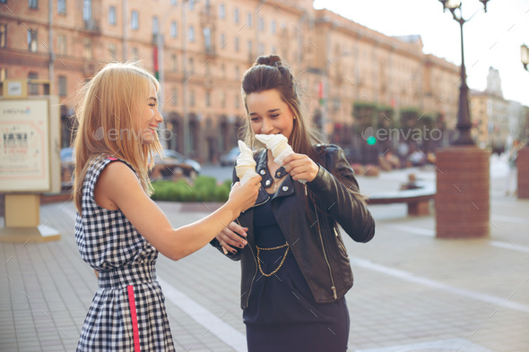 Two best friends having ice cream together outdoors. Young women eating ice cream and laughing. - Stock Photo - Images