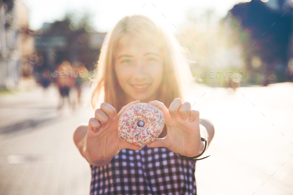 Smiling woman in summer holding donut - Stock Photo - Images