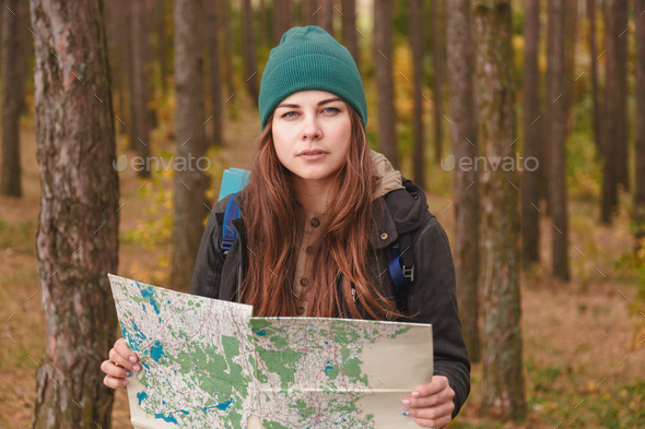 Woman with travel map and backpack in pine forest. - Stock Photo - Images