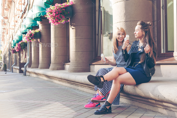 Two best friends having ice cream together outdoors. Young women eating ice cream and laughing - Stock Photo - Images