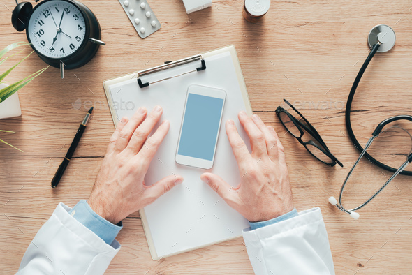 Doctor using smartphone app in hospital office - Stock Photo - Images