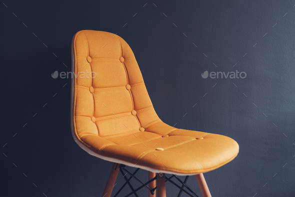 Empty generic yellow chair against waiting room gray wall - Stock Photo - Images